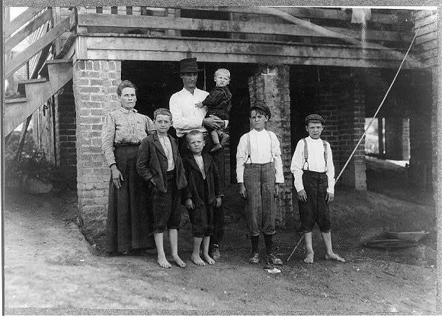 """S.D. Ison and family. Father works some. Both boys on right of photo have been in Washington Cotton Mills, Fries, Va., for four years. When I asked the smallest worker how old he was, he said, """"Don't know,"""" and looked at his father, who said, """"Going' on 14."""" (but he did not say how near to 14 he was).  Location: Fries, Virginia."""