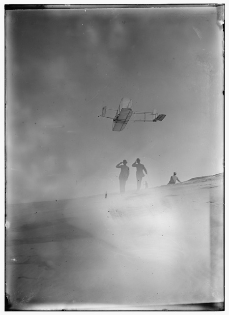 [Side view from below of Orville soaring in level flight, spectators looking up at glider; Kitty Hawk, North Carolina]