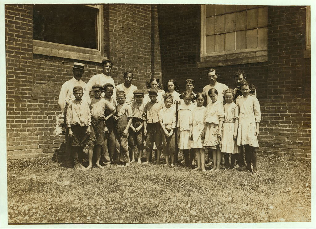 """Supt. and overseers with the """"Relief Crowd,"""" in Yazoo City (Miss.) Yarn Mills. The Supt. said, """"We relieve all children under sixteen for two hours a day except the doffers, who get plenty of time off. They go out and play."""" Then turning to the children he said, """"Now play."""" They eyed him blankly, """"Play wot?"""" """"Oh, play anything."""" Before they could do it, however, he had to pose them himself (see photo 2106) which was especially posed for the occasion. In this photo, note the disparity between the (alleged) ages of the younger ones who said that they were twelve and thirteen, and the older ones, who said fifteen years old.  Location: Yazoo City, Mississippi."""