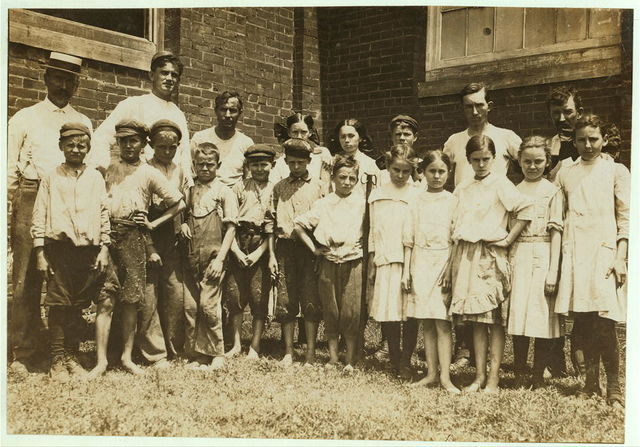 """Supt. and overseers with the """"Relief Crowd,"""" in Yazoo City (Miss.) Yarn Mills. The Supt. said, """"We relieve all children under sixteen for two hours a day except the doffers, who get plenty of time off. They go out and play."""" Then turning to the children he said, """"Now play."""" They eyed him blankly, """"Play wot?"""" """"Oh, play anything."""" Before they could do it, however, he had to pose them himself (see photo 2106) which was especially posed for the occasion. In this photo, note the disparity between the (alleged) ages of the younger ones who said that they were 12 and 13, and the older ones, who said 15 years old.  Location: Yazoo City, Mississippi."""