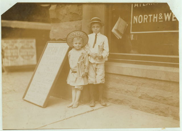 """""""Teaching the young Idea How to Sell."""" Gus Hodges, age 11, instructing his brother Julius, age 5. I found Gus selling as late as 9:00 P.M., and he said that he had made over one dollar a day. Julius and another brother, 9 years old, has made 25 cents that day.  Norfolk, Virginia."""