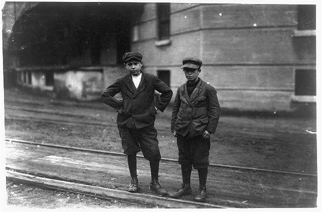 The two smallest boys in the group are Patrick Roddy, 968 Central Street, who doffs in No. 1 spinning room, and has been working there three months. Walter McNally, 7 North Street, works in No. 2, spinning room and appears 13 years old.  Location: Lowell, Massachusetts.