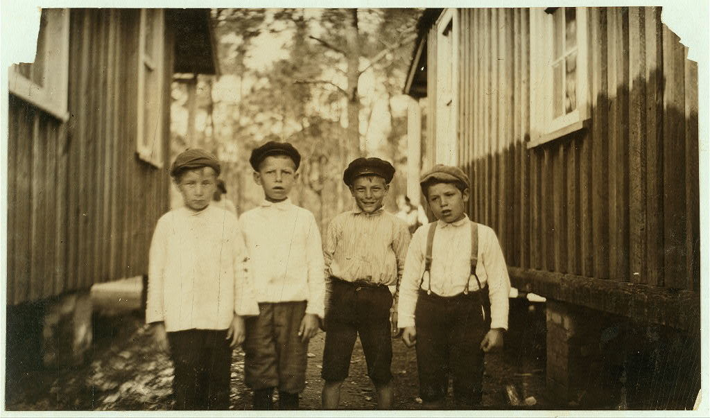 They all shuck oysters at Pass Christian. Boy on left end is George Wikowski, nine years old; next is John Collins; next is Steve Strupeck, who worked last year; on right hand end is Frank Obin, eight years old whom I found asleep on the floor of the shucking shed at 4 o'clock in the morning.  Location: Pass Christian, Mississippi.