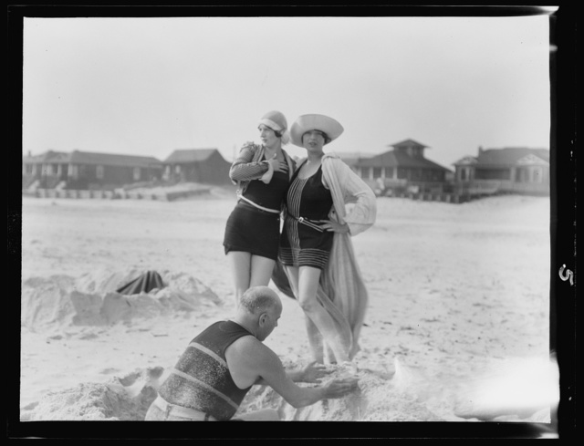 Unidentified man building sand castle and two women, Long Beach, New York