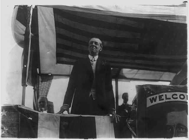[Woodrow Wilson, half length portrait, standing on platform, facing slightly left]