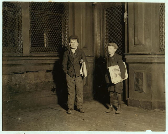 1:30 A.M. Peter, 15 years old (on left). Employed in camphor works. Air full of camphor. Sells papers Saturday nights until 3 A.M. One of a dozen boys who sleep in car barn these nights. Charles, 11 years old (on right). Gets supper in restaurant. Sells every day. Brother of #3117.  Location: Jersey City, New Jersey.