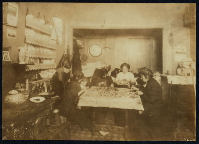 2 P.M. Mrs. Katie --- (refused to give their name), 134 1/3 Thompson St., one flight up, front. Making artificial flowers in a crowded and dirty room used as kitchen, bed room, living room, and work room. Mother and family work including 8 and 9 yr. old girls in the photo (who were at home 2 P.M. on a school day) and the little 3 and 4 yr. olds who were helping by separating the petals. See report on schedule. Name is Darelli [or Tarelli?] 3 days after photo was taken the home was sealed up and disinfected by Board of Health for tuberculosis; 14 yr. old boy. Immediately the flower making resumed again.  Location: New York, New York (State)