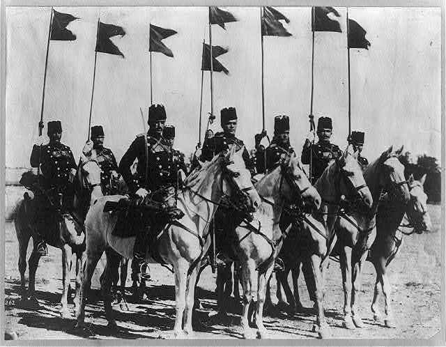 8 members of the Turkish cavalry on horseback with flags