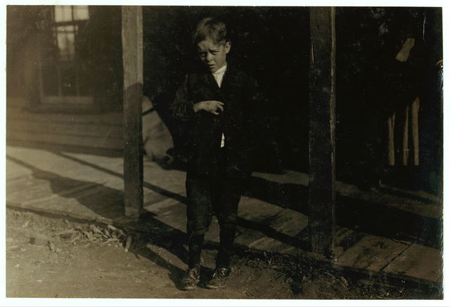 """Accident to young cotton mill worker. Giles Edmund Newsom (Photo October 23rd, 1912) while working in Sanders Spinning Mill, Bessemer City, N.C. August 21st, 1912, a piece of the machine fell on to his foot mashing his toe. This caused him to fall on to a spinning machine and his hand went into the unprotected gearing, crushing and tearing out two fingers. He told the Attorney he was 11 years old when it happened. His parents are now trying to make him 13 years old. The school census taken at the time of the accident makes him12 years (parents' statement) and school records say the same. His school teacher thinks he is 12. His brother (see photo 3071) is not yet 11 years old. Both of the boys worked in the mill several months before the accident. His father, (R.L. Newsom) tried to compromise with the Company when he found the boy would receive the money and not the parents. The mother tried to blame the boys for getting jobs on their own hook, but she let them work several months. The aunt said """"Now he's jes got to where he could be of some help to his ma an' then this happens and he can't never work no more like he oughter.""""  Location: Bessemer City, North Carolina."""