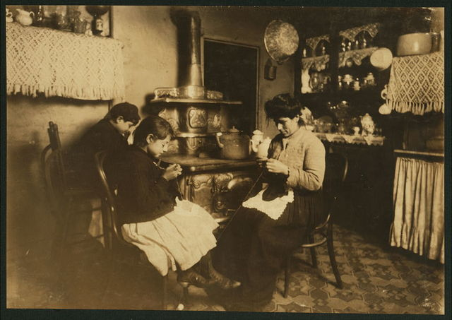 """Antoinette Fazzino, ten years old, makes Irish lace for collars and waists, after school. Her younger brother (by the stove) said, """"Lace is too dam-cheap."""" Antoinette wears glasses. 303 E. 149th Street, N.Y.  Location: New York, New York (State)"""