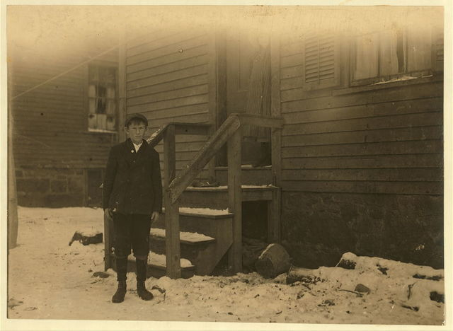 Bad housing and congestion. Mikeal Wikbas [or Wikras?], (about 14 years old) at doorway of home. 3 Hampton Court. Works in Wamsutta Mill.  Location: New Bedford, Massachusetts.
