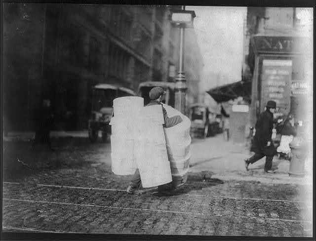 Boy carrying hats. Bleeker Street, N. Y.  Location: New York, New York (State)