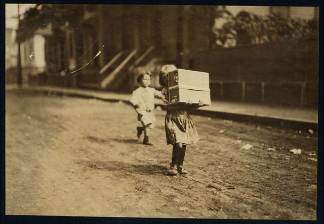 Carrying tags. A little tot with a heavy load.  Location: Roxbury, Massachusetts.