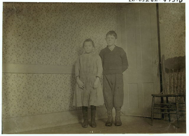 Compare ages: Veronica Mikula, says 12 years old, 93 N. Front St., Steven Mikula, (in mill) says 15 years, appears less than 14. Photo taken in spare unused room too cold to warm. They crowd together in kitchen.  Location: New Bedford, Massachusetts.