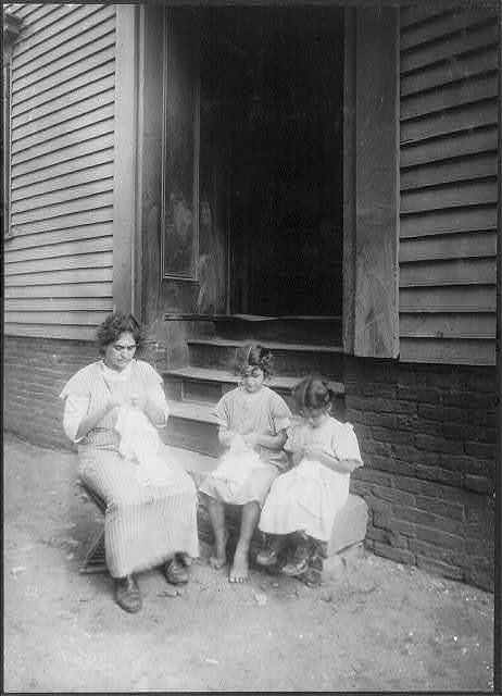 Crocheting on underwear at home. Carmina Caruso, 10 years old, a regular worker. Sister Mary, 5 years old, learning; mother and neighbor sitting out in unkept [i.e., unkempt?] side yard all day long. Sometimes they walk up and down the street as they work. 18 South Street, Somerville, Mass. See also home work report. See also home work report.  Location: Somerville, Massachusetts.