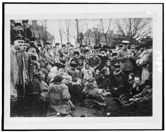 [Crowd of refugees(?)--, possibly Jewish, and three officials outdoors, Russia]