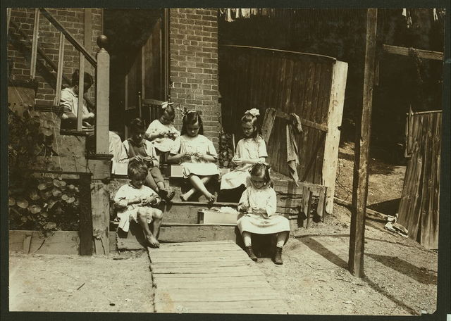 """Family of Mrs. Donovan, 293 1/2 Highland Street, Roxbury, Mass., tying tags for Dennison Co. This is the family that has worked on tags for 7 years and makes an average from that work $30. One month they made $42. Mrs. D. said: """"Will we ever be able to do it again?"""" All the children aged 13, 9, 11, 7 and the twins 4 1/2 years, help the mother. They often have to work late at night to get done. See Home Work report.  Location: Roxbury, Massachusetts."""