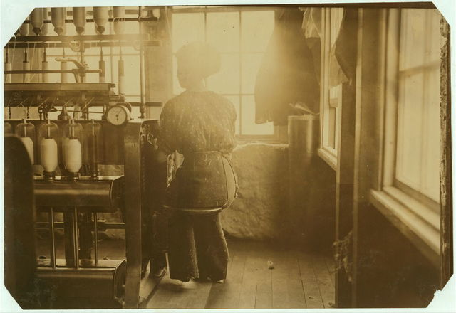 (For Child Welfare Exhibit 1912-13.) Cotton-mill employee using seat that is on the end of her machine.  Location: Pawtucket, Rhode Island.