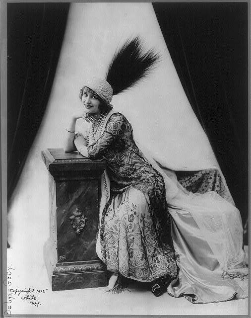 [Gaby Deslys, 1884-1920, full length portrait, seated, facing left, wearing feathered hat and fancy dress]