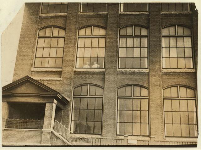 Girls flirting through window of Manomet Mill.  Location: New Bedford, Massachusetts.