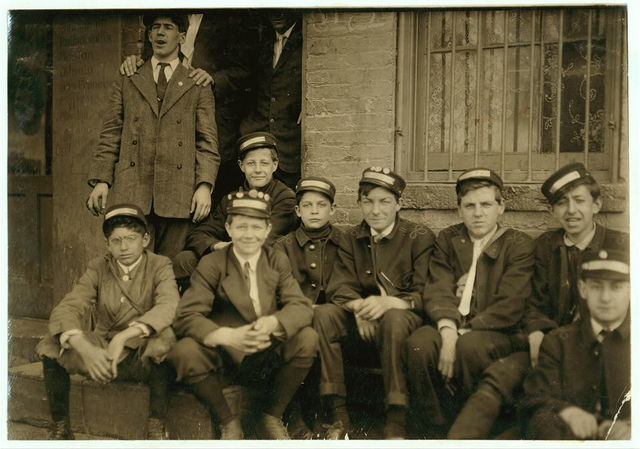 """Group of Dime Messengers Service boys, 1228 H St., N.W., at the main office. The youngest boys are Eddie Tahoory (14 yrs. old) . Said to be a recent comer. Lives, 108 Fourth St., N.E., and Earle Griffith (15 yrs. old), 107 Fifteenth St., N.W., Washington, D.C. From a questionable home. Mother eloped with boarder. Took children with her. They said they never know when they were going to get home at night. Usually work one or more nights a week, and have worked until after midnight. They said last Christmas their office had a 9 yr. old boy running errands for them, and that he made a great deal of money from tips. They make about $7 a week and more, sometimes. Said """"The office is not allowed to send us into the red light district, but we go when a call sends us. Not very often.""""  Location: Washington (D.C.), District of Columbia."""