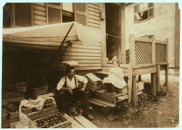 Home and fruit stand of the Cavicchio family. 64 Bedford Street. Somerville, Mass. Both the mother and Mary, 10 years old, worked off and on all day out here with the soot from the passing engines dropping so fast it had to be shaken off. A new tunnel is being dug in front of the house. Mother and Mary tend the fruit stand while crocheting and the work is thrown over the railing and fence near by. Their garments are filthy and grimy. See also Home Work report.  Location: Somerville, Massachusetts.