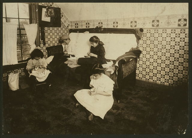 Home of Peter Mazkerthlain, 7 Elizabeth St., Worcester, Mass. Children: 6 yrs., 9 yrs., 11 yrs., 12 yrs. old, working on garter buttons. Mother works too. Make $1.50 to $2.00 a week. Neighbors say she keeps them at work late at night. (See also Report.) Photo at noon. Witness, F.A. Smith.  Location: Worcester, Massachusetts.