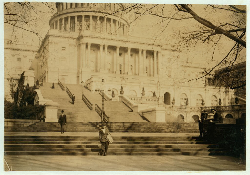 How insignificant a newsie is in comparison with matters of State. Peter Pepe, 24 Wonders Court, 10 yr. old newsie, selling on the Capitol steps. Been selling for 2 yrs. Makes 20 cents a day. His father is lounging at the left of the photo at the side of pillar. The boy begins selling at 5 A.M., Sundays.  Location: Washington (D.C.), District of Columbia.