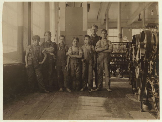 In this group are some of the youngest workers in Spinning Room of Cornell Mill. The smallest is Jo Benevidos, 5 Merion St. Other small ones are: John Sousa, 84 Boutwell St., Anthony Valentin, 203 Pitman St. Manuel Perry, 124 Everett St. John Travaresm [or Taveresm?], 90 Cash St. The difficulty they had in writing their names was pathetic. When I asked the second hand in charge of the room to let the boys go outside a moment and let me get a snap-shot he objected, saying they would stay out and not be in shape to work. When they carry dinners, they breathe the close air of the spinning room from 7 A.M. to 5:30 P.M. with no let-up. Cornell Mill.  Location: Fall River, Massachusetts.