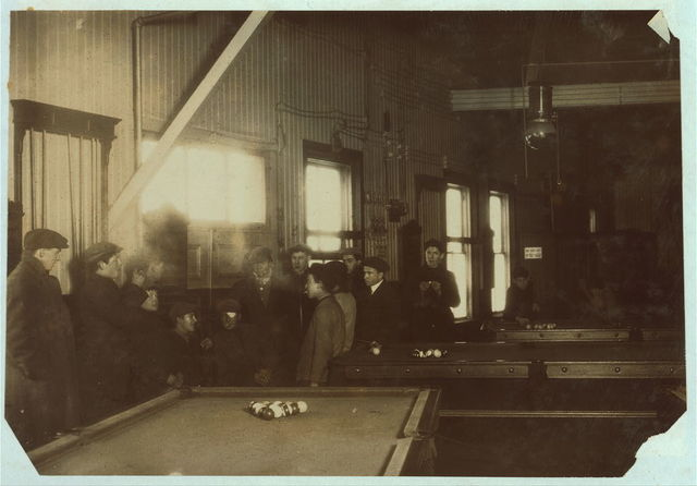 Killing time. Boys and men (many of them workers) hanging around Swifts' Pool Room. Saturday P.M. A common sight any day. Educational influences bad: stories and remarks will not bear repetition. Mill boys and men.  Location: Fall River, Massachusetts.
