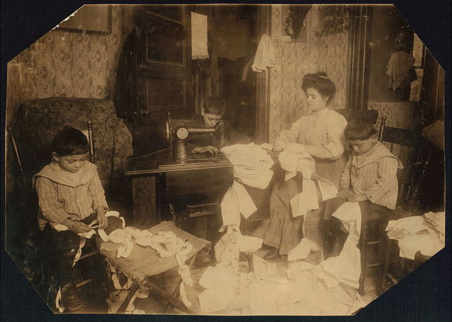 Making dresses for Campbell Kid Dolls in a dirty tenement room, 59 Thompson St., N.Y., 4th floor, front--Romana family. The little boys, 5 and 7 years old, help to break the threads, the older boy, about 12 years old, operates the machine [when] the mother is not using it.  Location: New York, New York (State)