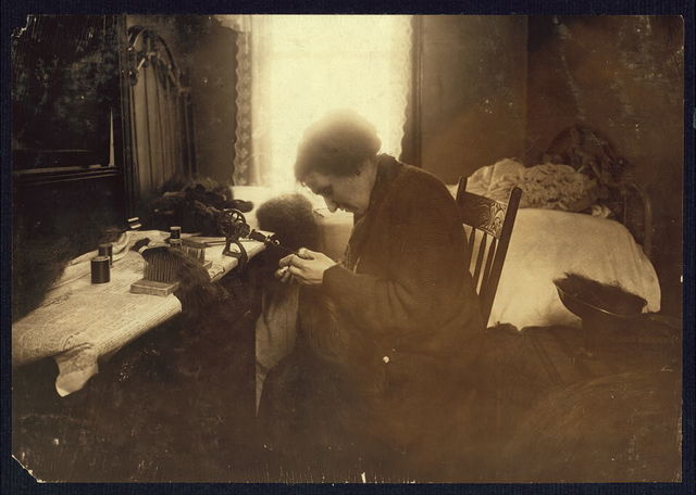 Making hair-goods in a tiny hall-bedroom. Mrs. Chassin, 385 E. 3rd St., N.Y. top floor. The whole tenement is in a most dilapidated and disreputable state. Hair lying on the bed, trunk and bureau. Mrs. Chassin used to keep a shop herself but now works for a Delancy St. firm. Says she makes about $12 a week.  Location: New York, New York (State)