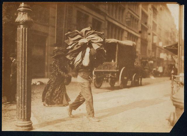 Man carrying bundle of garmets. Bleeker Street, N.Y.  Location: New York, New York (State)