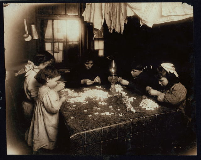 Mortaria family, 8 Downing St., N.Y., making flowers wreaths. The Little three-year-old on left was actually helping, putting the center of the flower into the petal, and the family said she often works irregularly until 8:00 P.M. The other children, 9, 11, and 14 yrs. old work much later (until 10:00 P.M.) The oldest girl told me her father is a soap-maker and has been making $3.00 a day steady for three years. They told the same to the other investigator. (See also 2875.) 5 P.M.  Location: New York, New York (State)