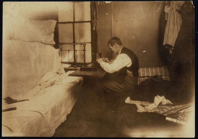 Mr. Rothenberg stitching neckties in small inner bed-room. See photo and label 2877.  Location: New York, New York (State)