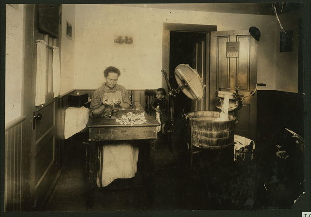 Mrs. Eugene Lampron, Reservoir Street, Leeds, Mass., putting the bristles into tooth brushes in the kitchen of her home. She has been doing it for 9 years, and showed the effect of it. See also Home Work report.  Location: Leeds, Massachusetts.