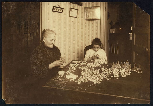 """Mrs. Montemora, Fifty-five years old, is janitress for a large tenement, 133 W. Houston St., (lives Apt. 7) housing 26 families. When not tending the furnace or occupied with other duties for others and her own family, she makes flowers, assisted by her niece Josephine, 12 years old. They both work until 10:00 P.M. frequently. Photo was taken at 2:30 P.M., Feb 2, 1912, a school-day, and their only explanation was, """"She just stayed out."""" Making buds. Several adult men relatives live with them. The flowers bring in only a dollar or two a week.  Location: New York, New York (State)"""