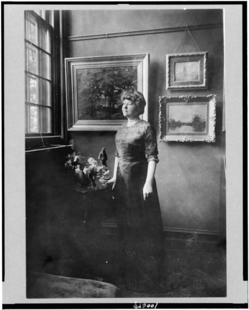 [Mrs. Woodrow Wilson (Ellen Louise Axson), full-length portrait, standing by window in room with paintings, facing left]