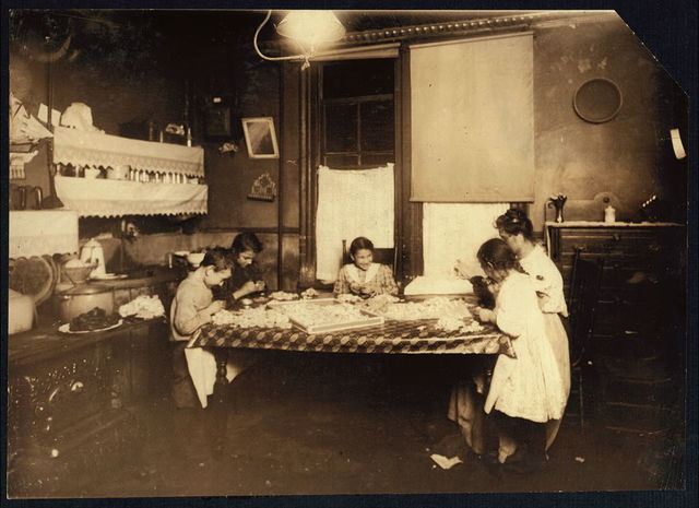 Night scene. 7:30 P.M. January 29, 1912. Making violets, and they often work later. Pollinni family, 5 Carmine St., N.Y. living in a reary [i.e., rear.] tenement. The six year old helps some. The eight, ten, and twelve year olds work later than this at times. Brothers, 15 and 17 years old, work in factory.  Location: New York, New York (State)