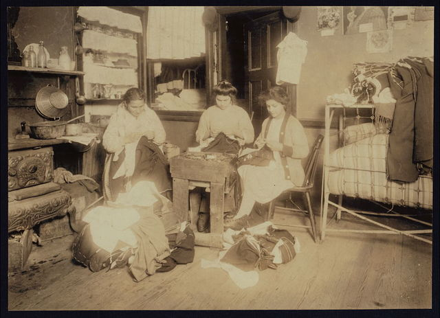 """Pallagi (?) family finishing pants, 17 Monroe St., N.Y., 2nd floor front. None of them spoke any English. A neighbor's child said the young girl is 13 yrs. old. Photo taken at 2:45 P.M. Mar./6/12, a school day. In the next apartment, a 12 yr. old girl was finishing pants and explained, """"I came home with the toothache.""""  New York, New York (State)"""