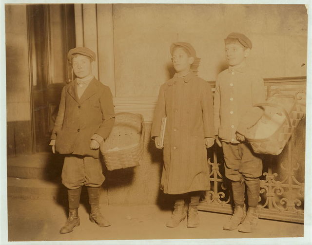 "Pretzel and gum vendors - Newsies are good customers. A boy sells a basketful of pretzels every afternoon at the ""news"" office, to the boys getting their afternoon papers. Henry Schertzer, (left) 14 yrs. old. Abel Schertzer, (right) 12 yrs. old. Sam Tumin, (centre) 10 yrs. old. Sam sells gum, often till 10 P.M. Taken at 8:15 P.M.  Location: Newark, New Jersey."