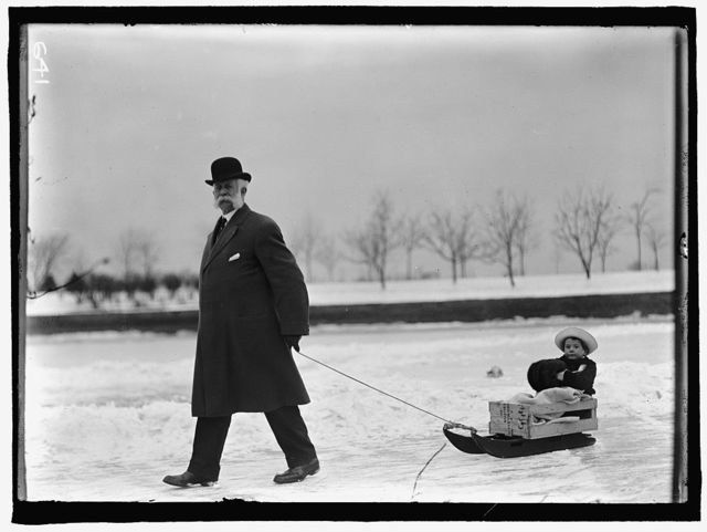 SKATING PARTY. UNIDENTIFIED MAN PULLING CHILD ON SLED