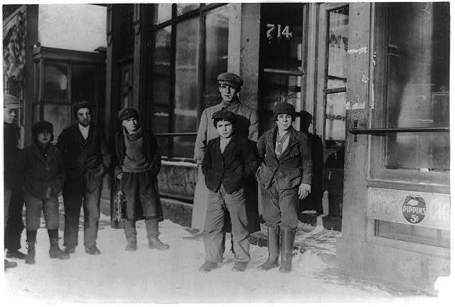 Smallest boy in front of man (in centre of photo) is Jo --- wouldn't give his name, very suspicious. He and the other boys said he is a sweeper in Acushnet Mill; lives at 697 S. Water St. Other boy in doorway is John Sousa, 641 S. Water St. John has been sweeper in Langshaw for two months.  Location: New Bedford, Massachusetts.