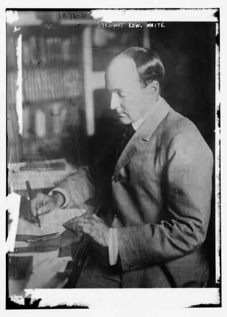 Stewart Edw. White at table writing