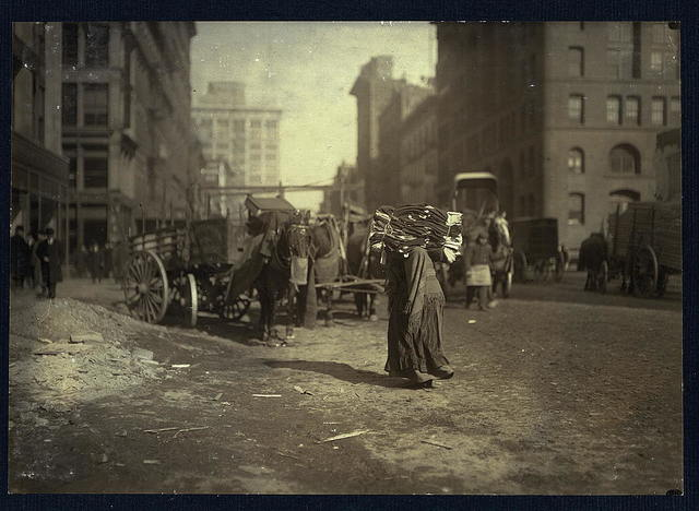 The breaking point. A heavy load for an old woman. Lafayette St., below Astor Pl., N.Y.  Location: New York, New York (State)