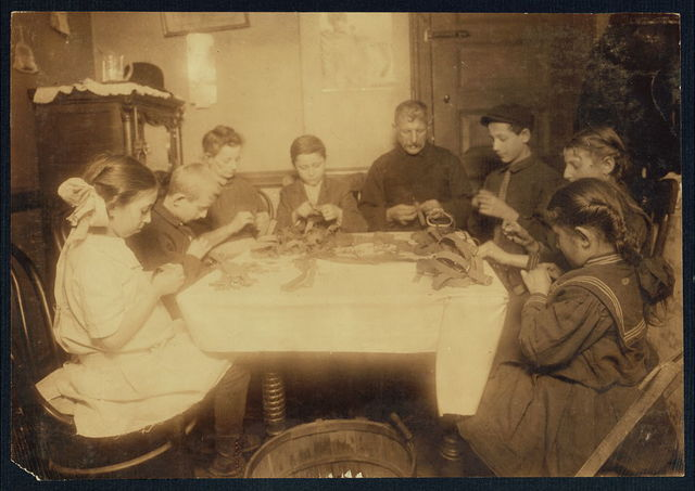 """These garters are made for Berger, 92 Spring St. 9:00 P.M., Feb. 27/12. Making garters (armlets). A Jewish family and neighbors working until late at night. This happens several nights in the week when there is plenty of work, the youngest children working until 9 P.M. and the rest until 11:00 or later. Family of Adolph Weiss, 422 E. 3rd St., N.Y., Seven-year-old Sarah, next is 11 yr. old sister. Next is 13 yr. old brother. On left is seven-year-old Mary and ten-year-old Sam, and next the mother is a 12 yr. old boy. The last three are neighbors children who come in regularly to work. """"It's better than running the streets"""" the father said. He was a grocery clerk but has been out of work for some months and works at home on the garters.  Location: New York, New York (State)"""