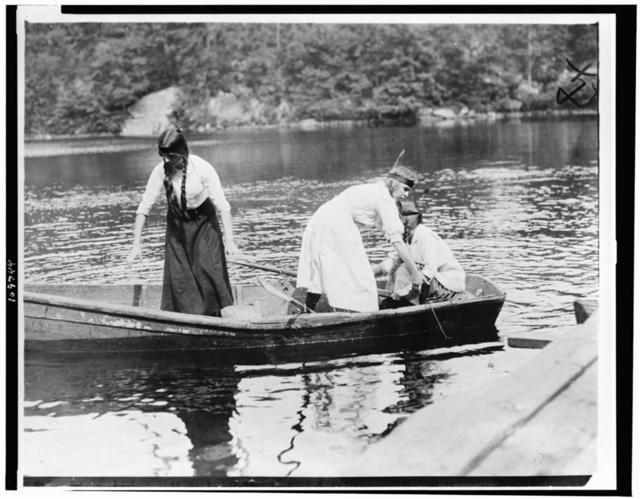 [Three Girl Scouts in boat at a camp]