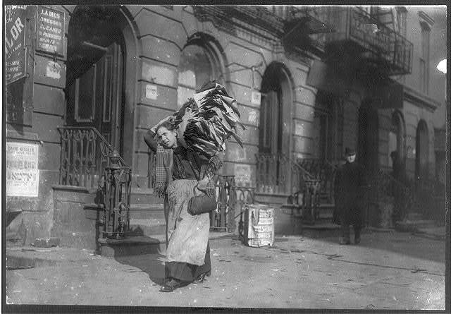 Tired woman with heavy load of home-work. Lafayette St., near Astor Place.  Location: New York, New York (State)
