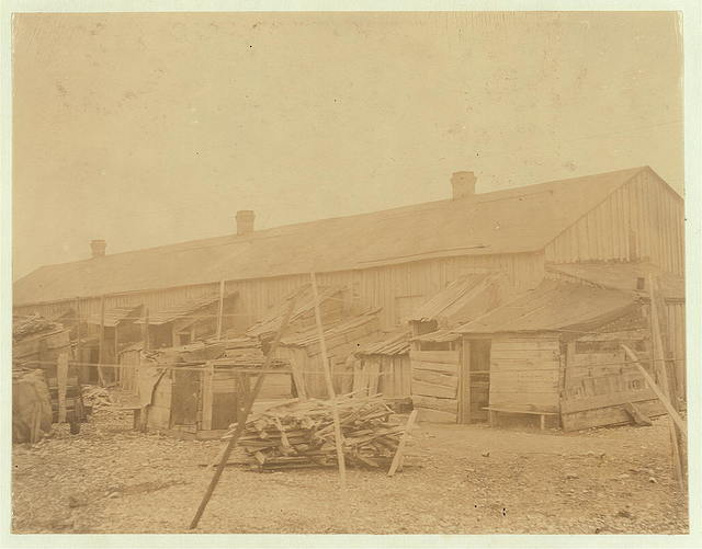 "[""We give them houses to live in."" About 50 persons housed in this miserable row of dilapidated shacks, located on an old shell-pile, and partly surrounded by a tidal marsh. Maggioni Canning Co.]  Location: [Port Royal, South Carolina]"