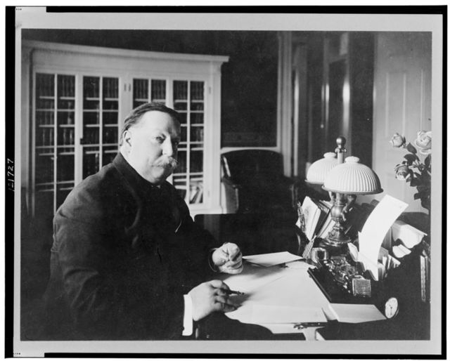 [William Howard Taft, half-length portrait, seated at desk, facing right, with pen and eyeglasses in his hands]